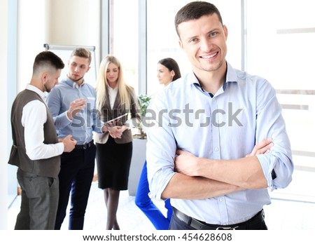 Happy smart businessman with team mates discussing in the background - stock photo