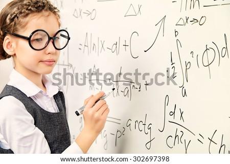 Happy smart schoolgirl in big glasses performs the task at the blackboard. Education. - stock photo