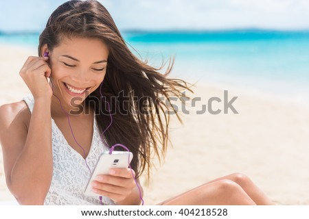 Happy smartphone woman listening with earbuds to streaming music. Young Asian casual girl using her mobile phone app 4g data to play songs while relaxing on beach summer vacations. - stock photo