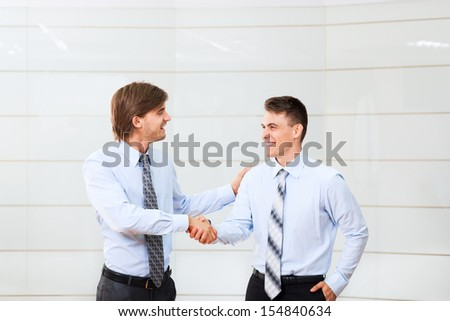 happy smile businessmen handshake standing at office, two businesspeople hand shake, business people congratulating men partner, meeting at conference hall