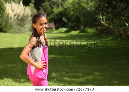 Happy smile from mixed race young school girl in park sunshine
