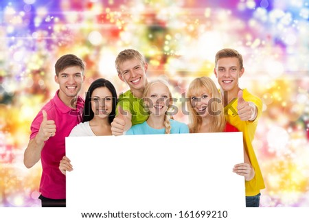 Happy smile group of young people holding a blank white card board, signboard, show thumb up gesture empty bill board over abstract colorful lights background - stock photo