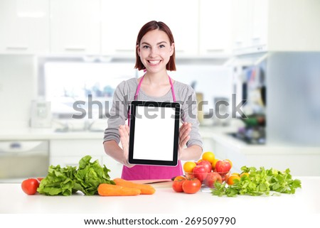 Happy smile woman in kitchen holding tablet pc computer with health food, empty computer screen is great for your design - stock photo