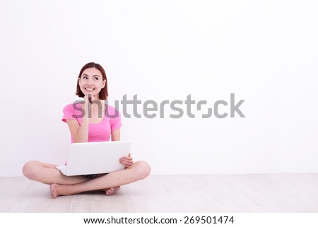 Happy smile young woman student girl using laptop computer pc and sit on the floor with white wall background, great for your design or text - stock photo