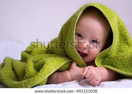 Happy, smiled half-year baby girl in a towel after bathing. - stock photo