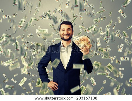 happy smiley businessman standing under money rain and holding euro - stock photo
