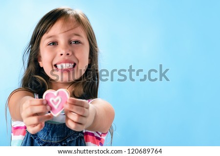 Happy smiling adorable young girl in denim dungarees holds out a pink heart shape cookie, valentines or mothers day concept - stock photo
