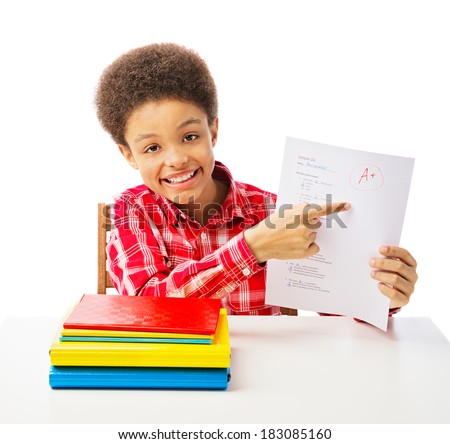 Happy smiling African American school boy, teenager point at A grade on the test, school and education concept. Isolated, over white background with copy space - stock photo