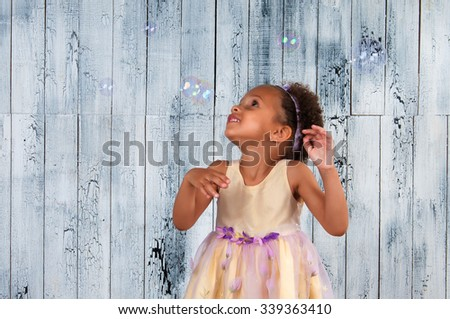 Happy smiling african  girl blowing soap bubbles on the background of wooden wall - stock photo