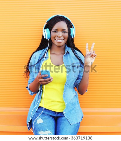 Happy smiling african woman with headphones enjoying listens to music over orange background - stock photo