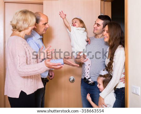 Happy smiling aged couple meeting kids and grand children at doorstep - stock photo