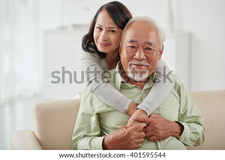 Happy smiling aged woman hugging her husband from behind - stock photo
