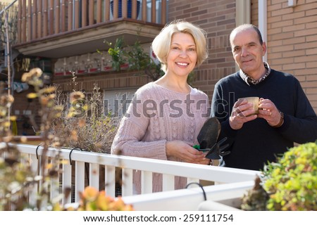 Happy smiling aged woman with horticultural sundry and aged man drinking tea in patio. Focus on woman - stock photo