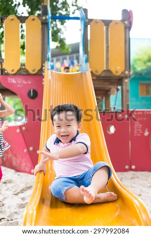 Happy smiling and handsome indian kid having fun playing in slider at a park on a bright sunny day. - stock photo