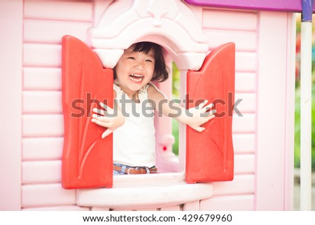 Happy smiling and pretty asian kid having fun playing in a park on a bright sunny day - stock photo