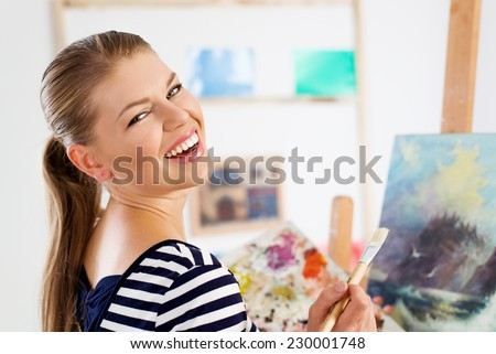 Happy smiling artist woman painting on canvas with acrylic colors. Young lovely Caucasian female applying new painting technique on her picture.