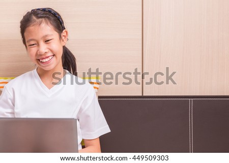 Happy smiling asian girl using notebook computer to study on her bed room for copy space text