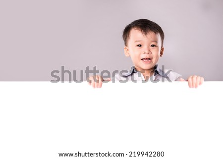 Happy smiling asian kid, boy, showing blank placard board to write it on your own text isolated on white background. Baby child with a white board isolated in white