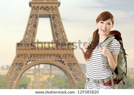 Happy smiling Asian woman travel and look at you in front of famous landmark, Eiffel tower in Paris, France. - stock photo
