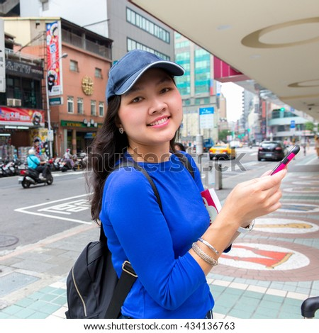Happy smiling Asian young female with using smartphone in ximending Taipei Taiwan, Asia.