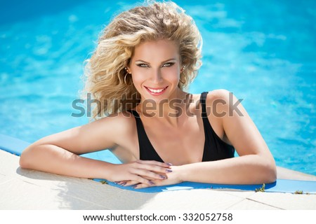 Happy smiling attractive blond woman in blue water swimming pool, Sensual model with curly hair posing at sunny day. Outdoor portrait. - stock photo