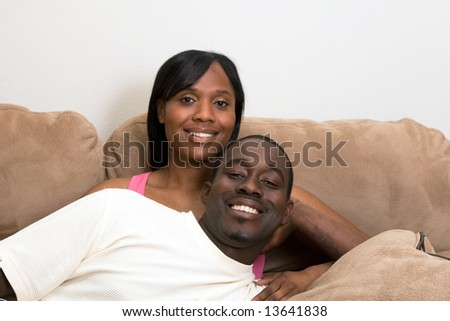 Happy, smiling, attractive couple on a couch. He is lying across her lap. Horizontally framed photograph.