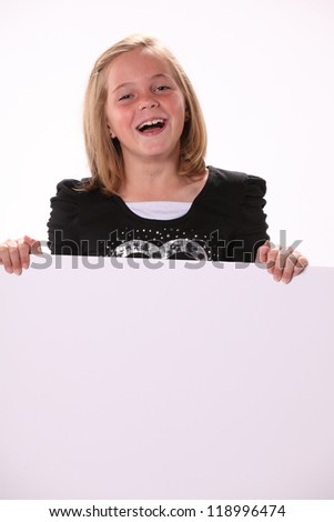 Happy smiling attractive preteen 10 year old female girl holding a white sign isolated against a white background.