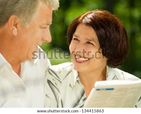 Happy smiling attractive senior couple reading together, outdoors