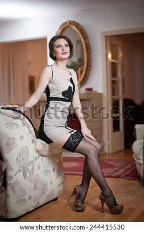 Happy smiling attractive woman wearing an elegant dress and black stockings sitting on the sofa arm. Beautiful young sensual female with short tight fit dress and high hills shoes leaning on couch - stock photo