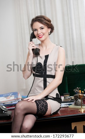 Happy smiling attractive woman wearing an elegant dress and black stockings talking by phone in an office scenery. Beautiful young sensual female with short dress sitting on desk holding the phone