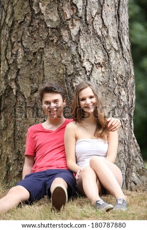 Happy smiling attractive young teenage couple sitting against a tree trunk enjoying a summer day together out in nature - stock photo