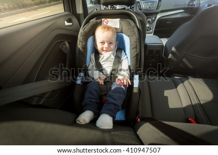 Happy smiling baby boy posing in child safety car seat