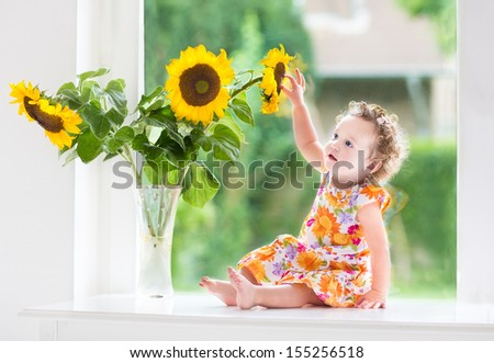 Happy smiling baby girl playing with beautiful sunflowers on a sunny summer day sitting at a window to the garden - stock photo