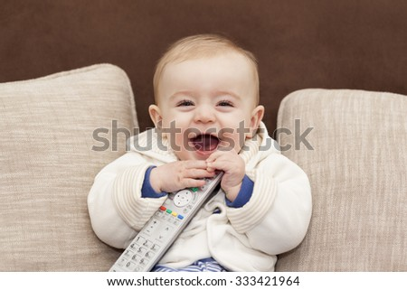Happy smiling baby holding a remote control tv - stock photo