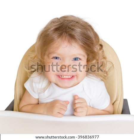 Happy smiling baby in the high chair. Isolated on white background.