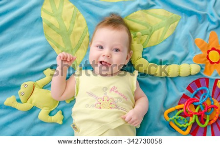 happy smiling baby lying on bright playing carpet - stock photo