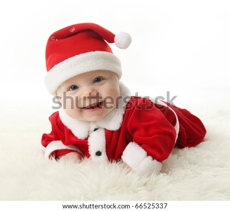 Happy Smiling baby lying on tummy wearing a red and white Christmas Santa hat and suit, isolated on a white background.