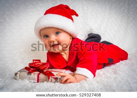 Happy smiling baby lying on white blanket with santa hat and suit - Christmas concept