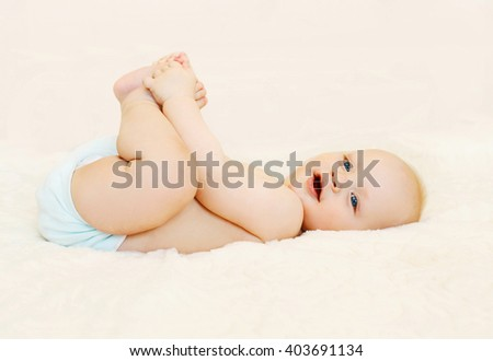 Happy smiling baby lying playing on the bed at home - stock photo