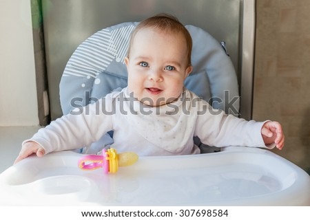 Happy smiling baby sitting on the highchair with the tray. Nibbler (food feeder) with the fruit in it lying on the tray. - stock photo