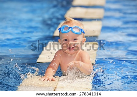 Happy smiling baby with first teeth and underwater goggles, playing with splashes in clear blue water in pool before swimming lessons, healthy lifestyle, summer activity and teaching children to swim - stock photo