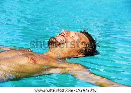 happy smiling beautiful man swimming in the water - stock photo