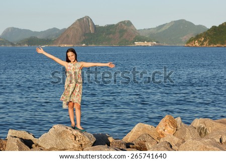 Happy smiling beautiful teen girl standing on stones in dress with long brown hairs near sea. Selective focus. Toning effect - stock photo