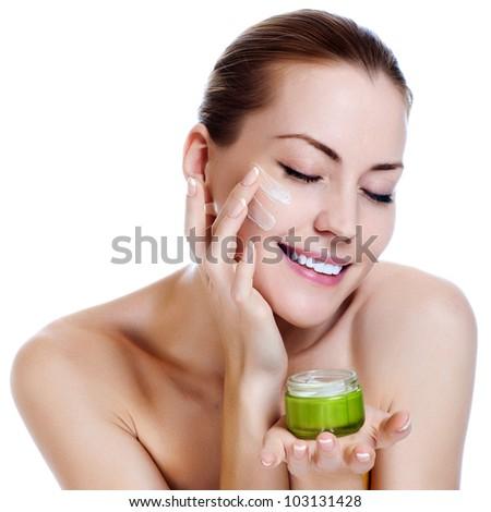 Happy smiling beautiful woman applying moisturizer cream on the face - stock photo
