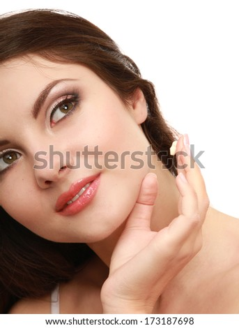 Happy smiling beautiful woman applying moisturizer cream on the face , isolated on white background