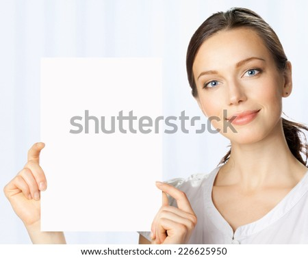 Happy smiling beautiful young business woman showing blank signboard, at office - stock photo