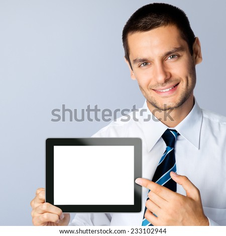 Happy smiling beautiful young businessman showing blank no-name tablet pc monitor, against grey background, with copyspace area - stock photo