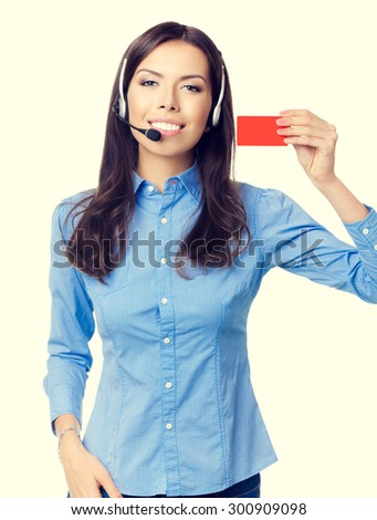 Happy smiling beautiful young customer support phone operator in headset, showing red blank business or plastic credit card - stock photo
