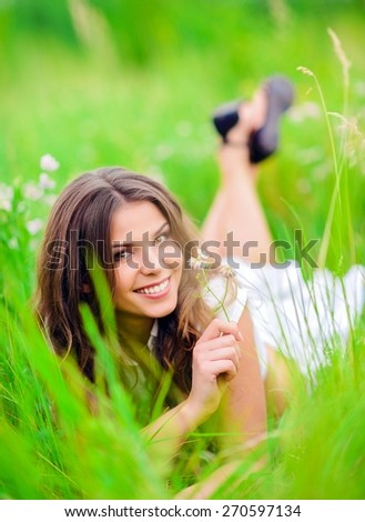 Happy smiling beautiful young girl lying among the grass and flowers - stock photo