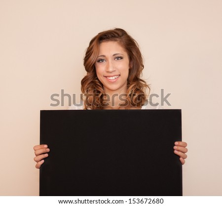 happy, smiling, beautiful young lady is holding up a blank black poster board with copy space for your message / Fill in the Blank - stock photo